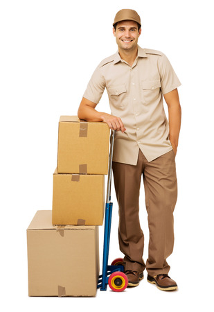 delivery service: Full length portrait of smiling deliveryman leaning on stacked cardboard boxes against white background. Vertical shot. Stock Photo