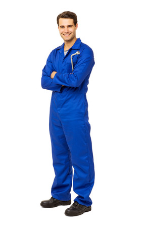Full length portrait of happy male mechanic in overalls holding wrench over white background. Vertical shot. Stock Photo