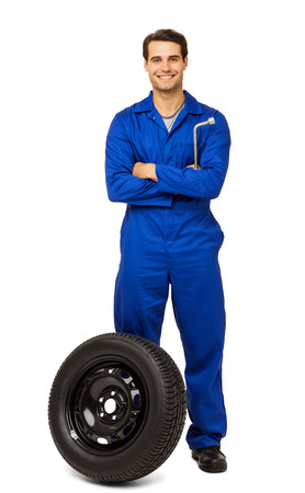 Full length portrait of happy male mechanic with spare tire over white background. Vertical shot. photo