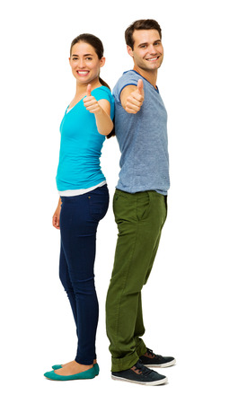 Side view portrait of happy couple gesturing thumbs up while standing back to back over white background. Vertical shot. photo