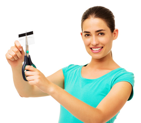 Portrait of beautiful young woman cutting credit card with scissor over white background. Horizontal shot. photo