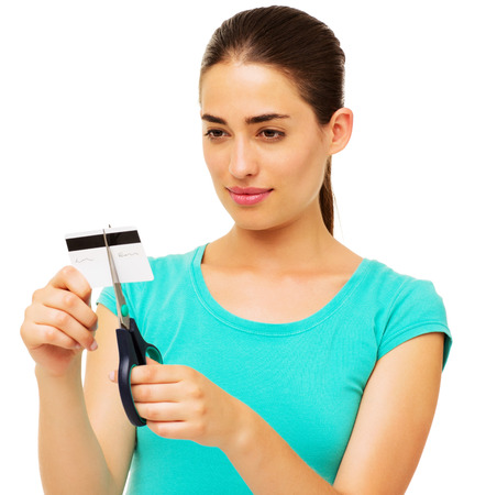 Beautiful young woman cutting credit with scissors over white background. Horizontal shot. photo