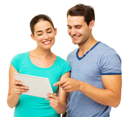 Happy young couple using digital tablet over white background. Horizontal shot. photo