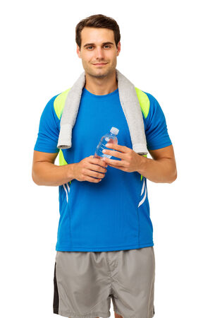 Portrait of fit young man holding water bottle standing isolated over white background. Vertical shot. photo