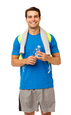 Portrait of smiling young man with towel and water bottle over white background. Vertical shot. photo