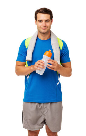 Portrait of confident young man with towel and water bottle standing isolated over white background. Vertical shot. photo