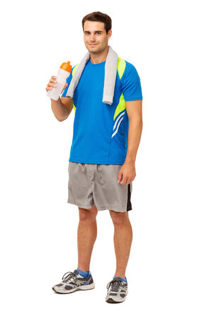 Full length portrait of confident young man drinking water after workout isolated over white background. Vertical shot. photo