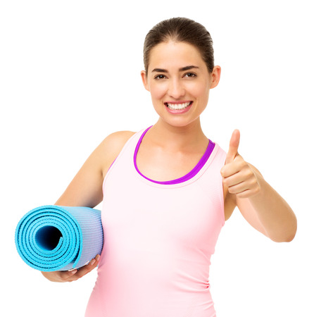 Portrait of happy young woman with yoga mat gesturing thumbs up over white background. Horizontal shot. photo