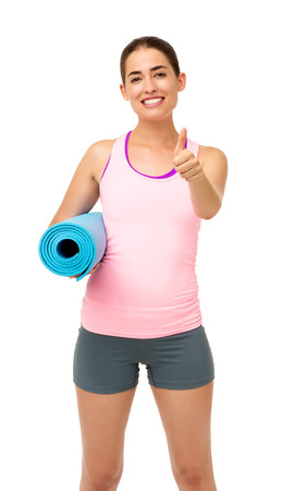 Portrait of happy young woman with fitness mat gesturing thumbs up over white background. Vertical shot. photo