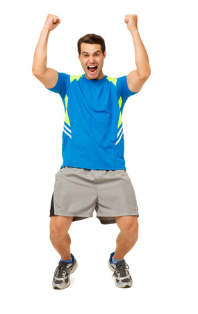 Full length portrait of excited young man in sportswear screaming with arms raised over white background. Vertical shot. Stock Photo
