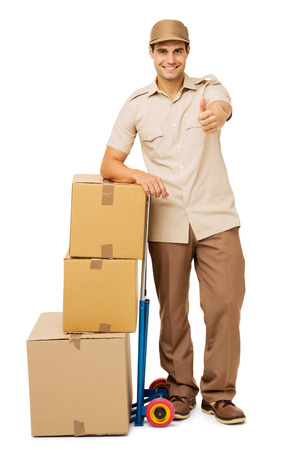 Full length portrait of confident deliveryman gesturing thumbs up while standing by stacked cardboard boxes over white background. Vertical shot. photo