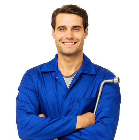 Portrait of happy male mechanic standing with arms crossed holding wrench over white background. Horizontal shot. Stock Photo