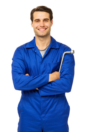 Portrait of confident male mechanic standing with arms crossed holding wrench over white background. Vertical shot.