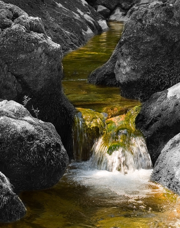 greenish: Greenish water flows on the decoloured stones forming a falls