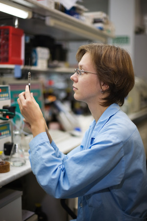 considers: The young nice woman-scientist considers the special syringe on a background scientific instruments Stock Photo