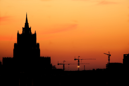 Silhouettes of a high-altitude building and three elevating cranes on a background of the beautiful sky.  photo