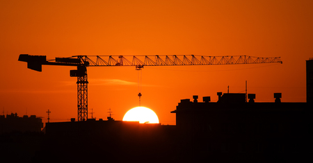 The elevating crane with a long arrow on a background of the red sky lifts a solar disk on a rope. photo