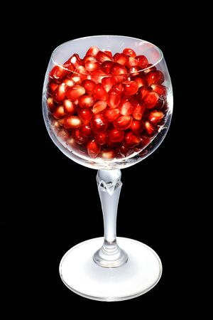 Pomegranate grainsglass in a glass. Isolated on black. photo