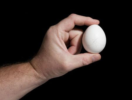 The hand holds an egg with cracks on a black background. The concept of destruction. photo