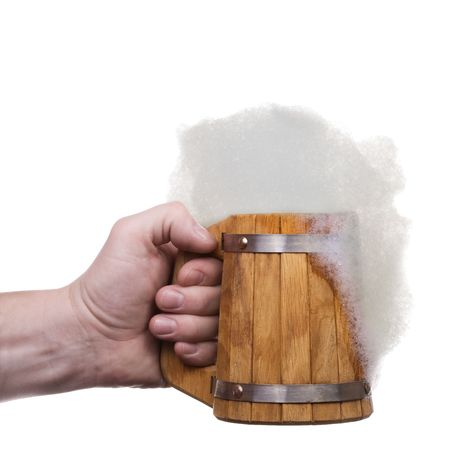 The mans hand holds big wooden beer mug collected from plates with froth. Isolated on white [with clipping path]. photo