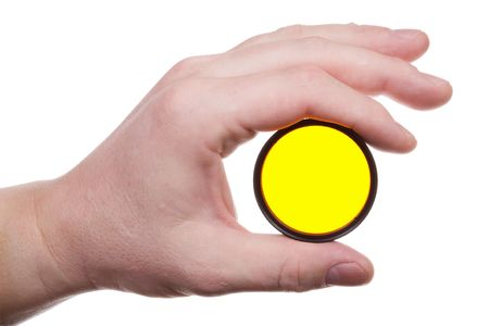 Mans hand holds a yellow optical filter. Isolated on white [with clipping path]. photo