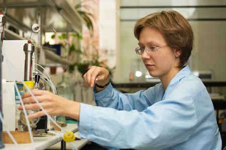 experimentation: The young nice woman-scientist work with syringe on a background scientific instruments Stock Photo