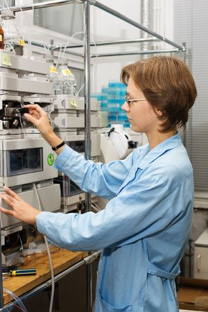 experimentation: The young nice woman-scientist work with scientific instrument on a background scientific instruments