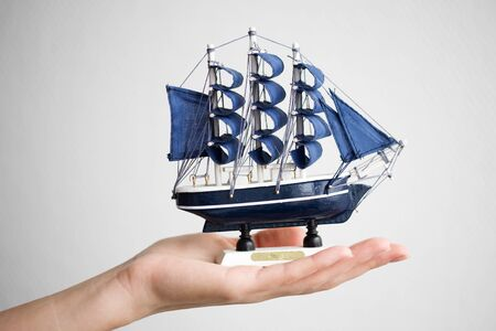 The hand holds a small ship.  photo