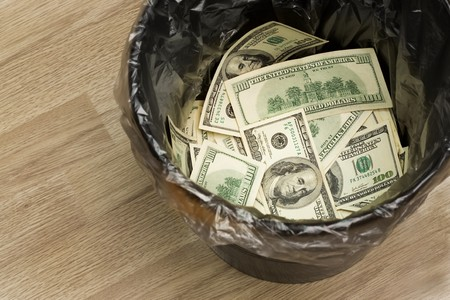 worthless: A money is in a trash bucket Stock Photo