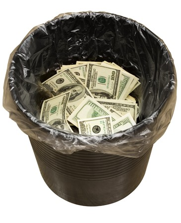 unnecessary: A money is in a trash bucket. Stock Photo