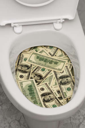 a lot of money: A lot of money is flushed down the toilet. Stock Photo