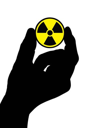 The silhouette of a mans hand holds a radiation sign. photo