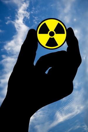 The silhouette of a mans hand holds a radiation sign on a background of the sky with clouds.  photo