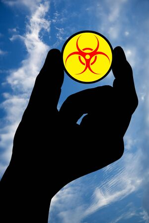 infectious waste: The silhouette of a mans hand holds a biohazard symbol on a background of the sky with clouds.