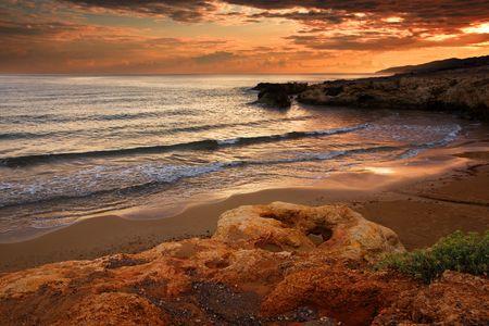 promontory: Sea coast on a sunset, crimson tone, a stone and waves. Stock Photo