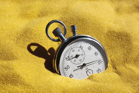 The old scratched stopwatch in yellow sand is covered by the sun. A metaphor of time.  photo