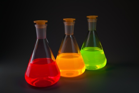 Chemical flasks with the liquids, shone different colors on a dark grey background. photo