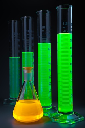 noxious: Graduated cylinders with a green fluorescing liquid of different height and yellow flask on a dark grey background. Shallow depth of field.  Stock Photo