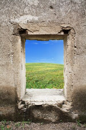 green grass and blue sky behind old castle window photo