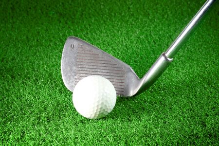 golf iron and golf ball on green grass photo