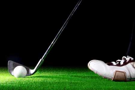 man ready to hit golf ball with golf iron on black background Stock Photo