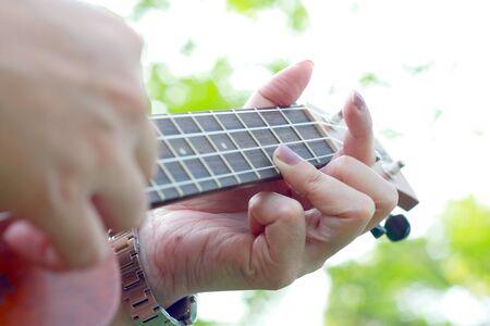 acoustical: hand playing ukulele