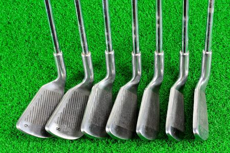 set of golf irons on green grass photo