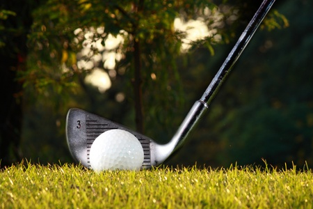 golf iron and golf ball on grass photo