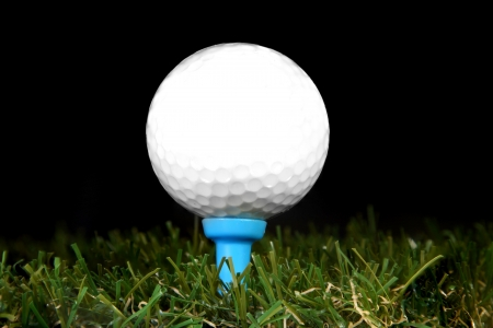 golf ball on a tee on black background
