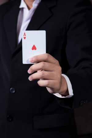 business man holding playing card on black background