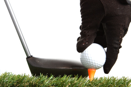 hand placing golf ball to a tee on white background photo