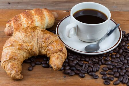 Breakfast with coffee, croissant and sausage dough on wooden table photo