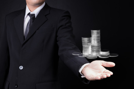 coin stack: business man showing coin stack