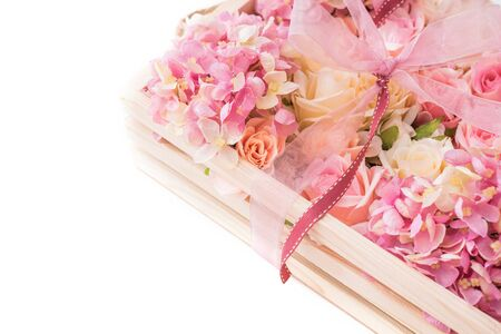 pink ribbon and pink flowers in wooden box